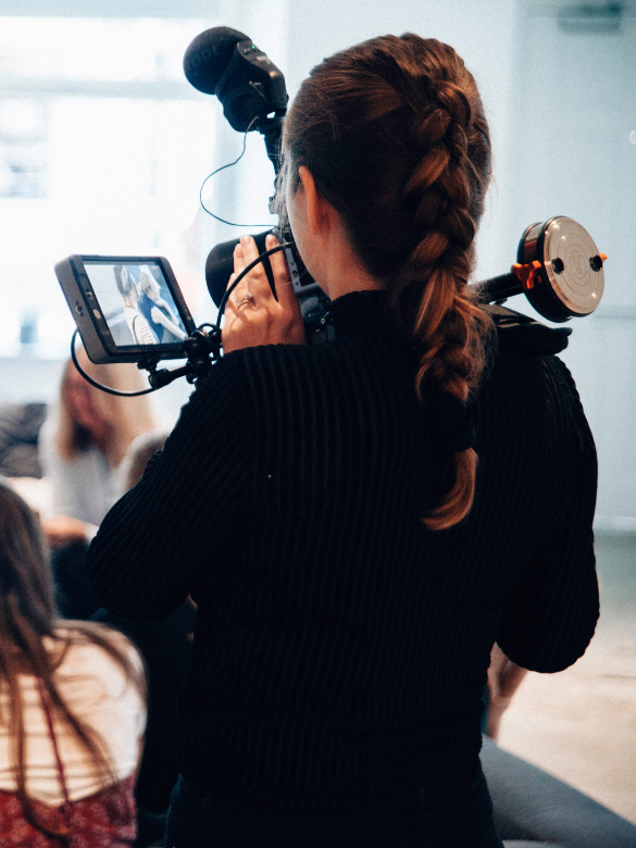 A student holds a large camera and records a scene for a short film.