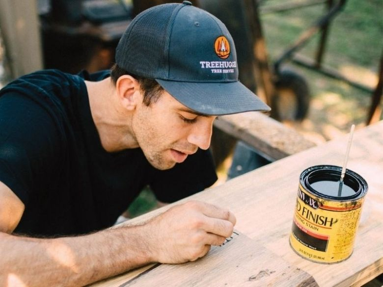 A male student leans over a wooden board, and a can of wood stain sits nearby.