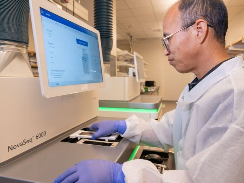 A man places a DNA sample into a sequencing machine.