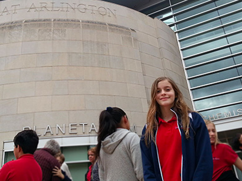 A student member of a class field trip smiles at the camera outside the UTA Planetarium.