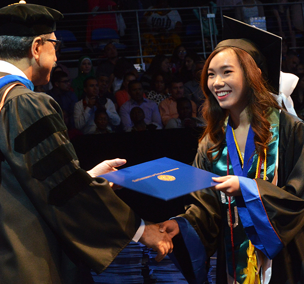 A female student receiving her degree from College of Science Dean Morteza Khaledi during commencement ceremony.