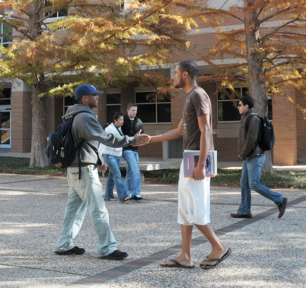 Two friends meeting on campus on a sunny fall day outside the Chemistry Research Building.