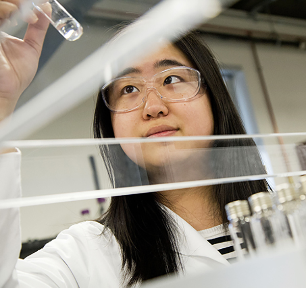 A female chemistry student wearing a lab coat and safety goggles observing a chemical in a test tube in a lab..