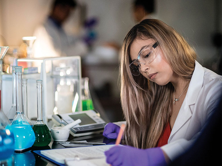A chemistry student writes notes in the lab.