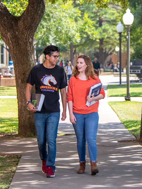 Two students walk through the quad at UTA carrying books.
