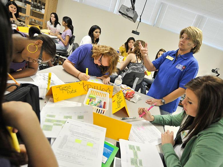 A UTeach Arlington teacher in the classroom talking with students.