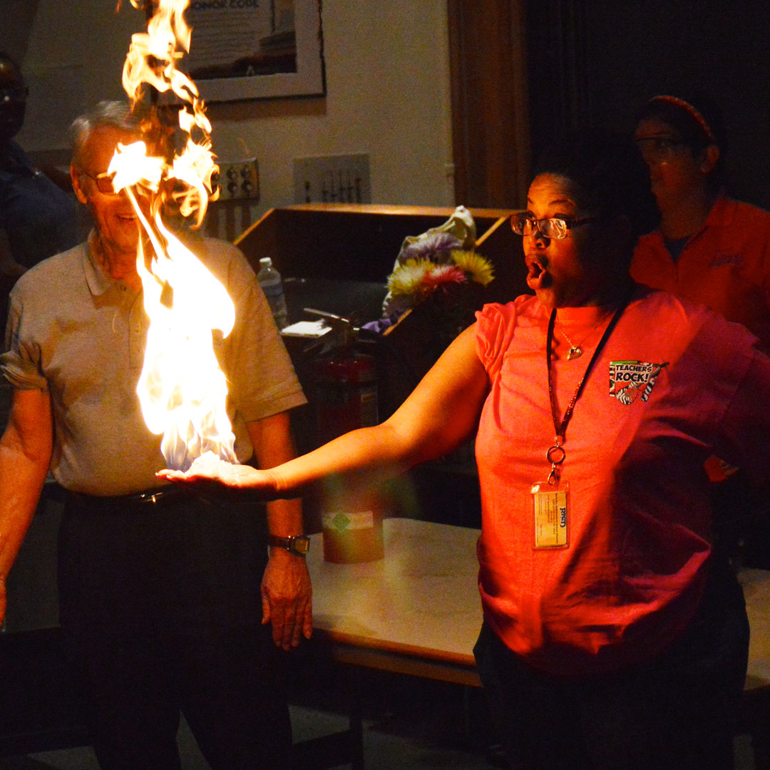 A student ambassador's hand is engulfed in flames (safely) during a show.