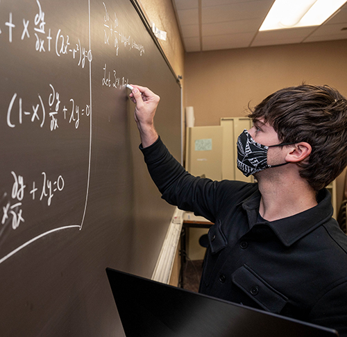 A male student wearing a mask writes math equations on a chalkboard.