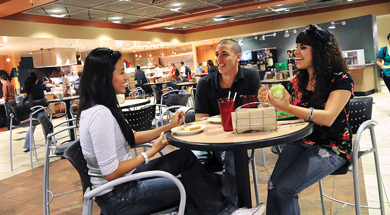 students eating at a table inside the u c