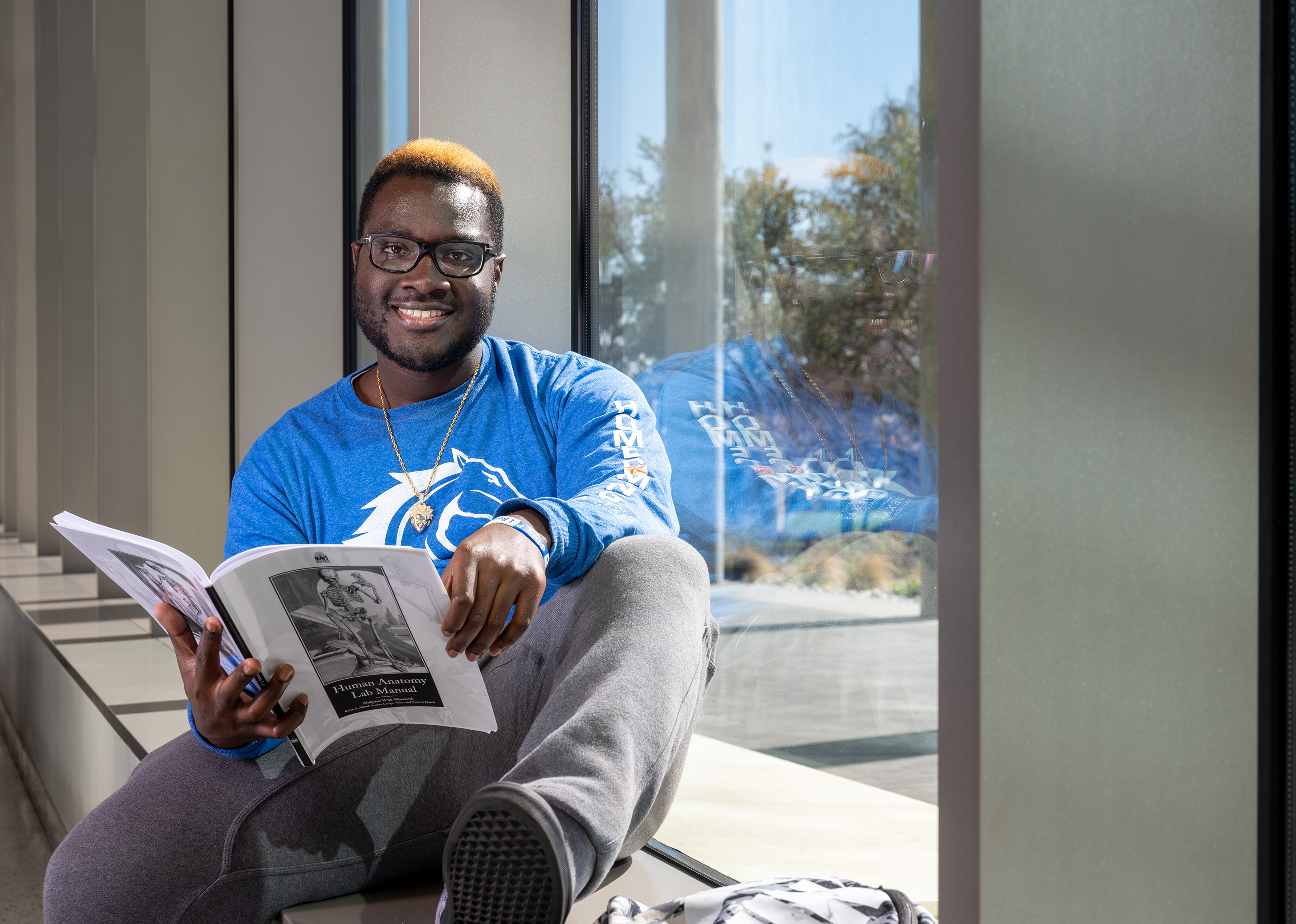 trevvion sheppard sitting in a window reading on campus