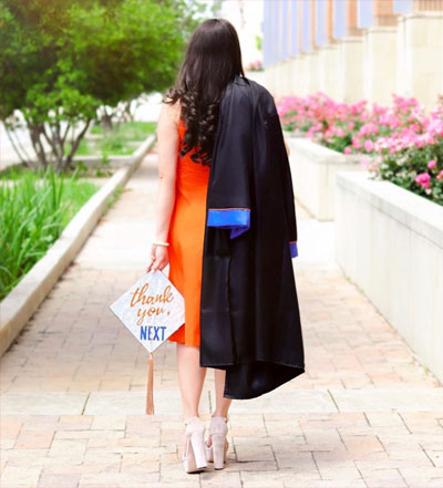 A UTA student walking away with graduation gown and cap in her hand