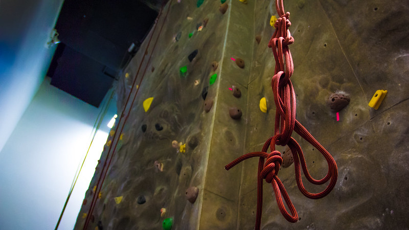 Climbing wall with a belay rope hanging from the ceiling