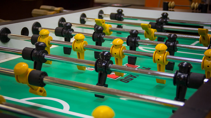 Close up shot of a Foosball table with yellow and black foosball players on rods.