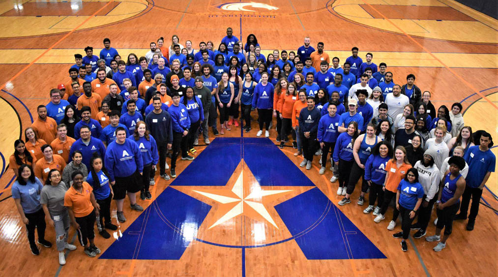Faculty and staff of Campus Rec circled around the UTA logo for a group picture