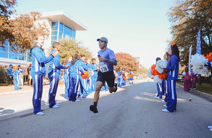 5K participant running towards the finish line as volunteers cheer him on