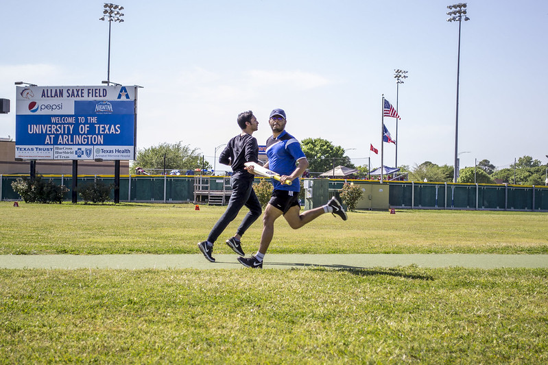 Two men passing each other during a game of intramural cricket
