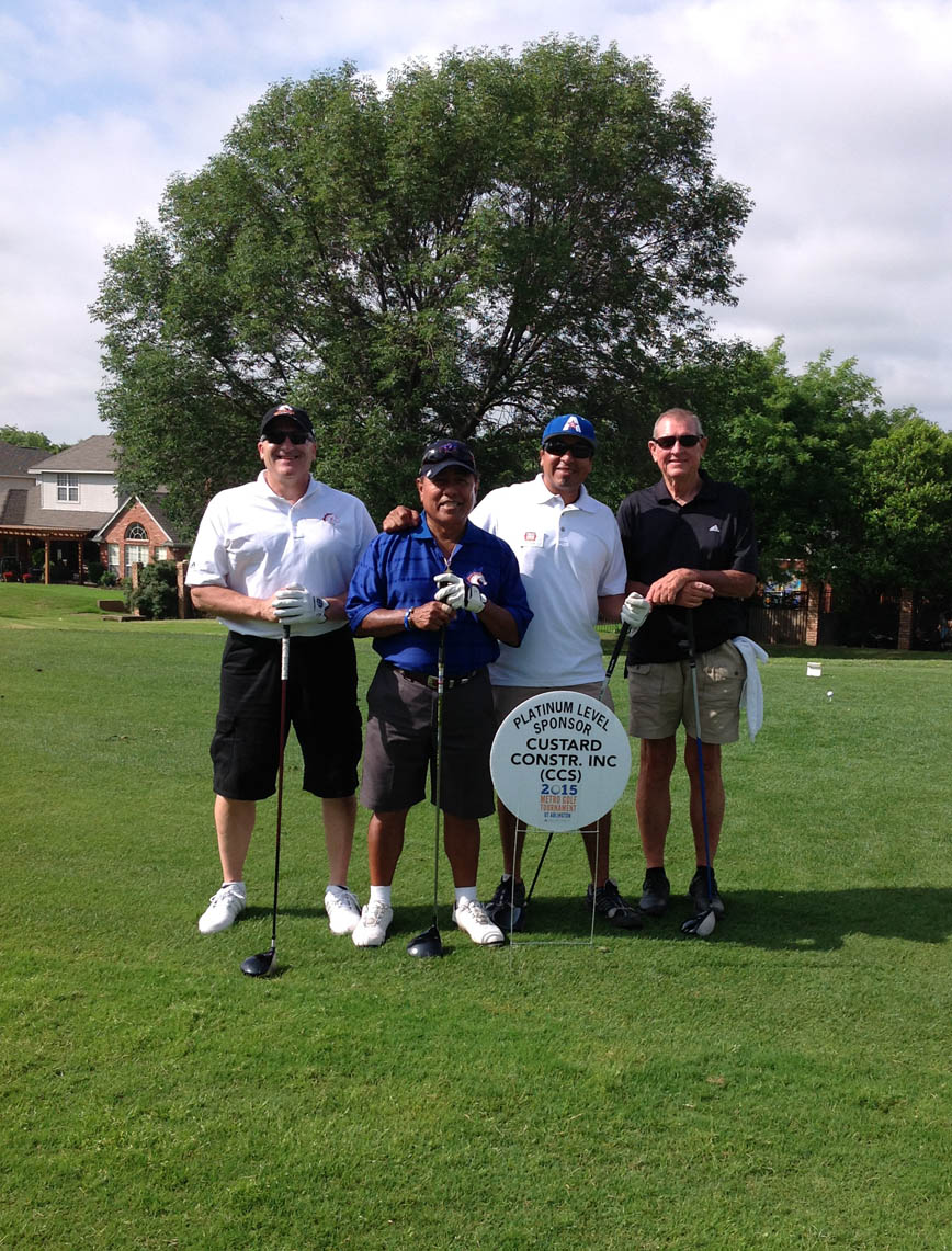 Participants of the Golf Tournament grouped with the event sign