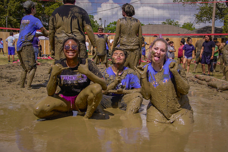 Oozeball contestants sitting in the mud on a hot day