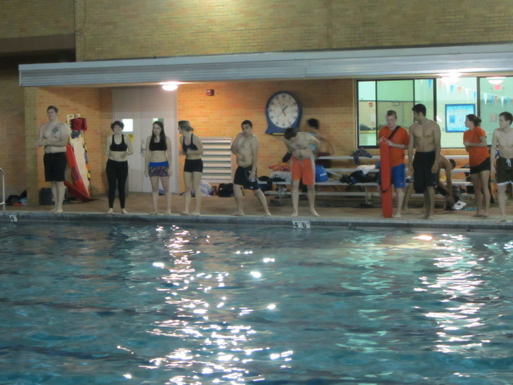 Students lined up the side of the indoor pool ready to jump in the freezing water