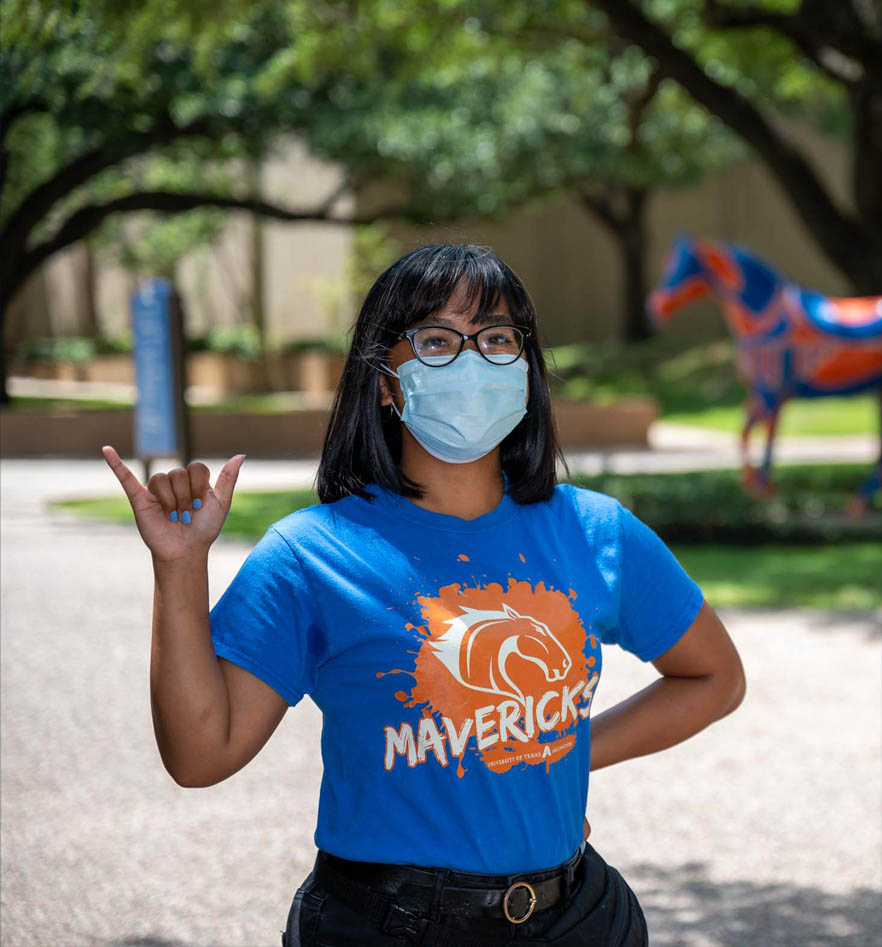 Kyra giving a mavs up in front of UTA horse