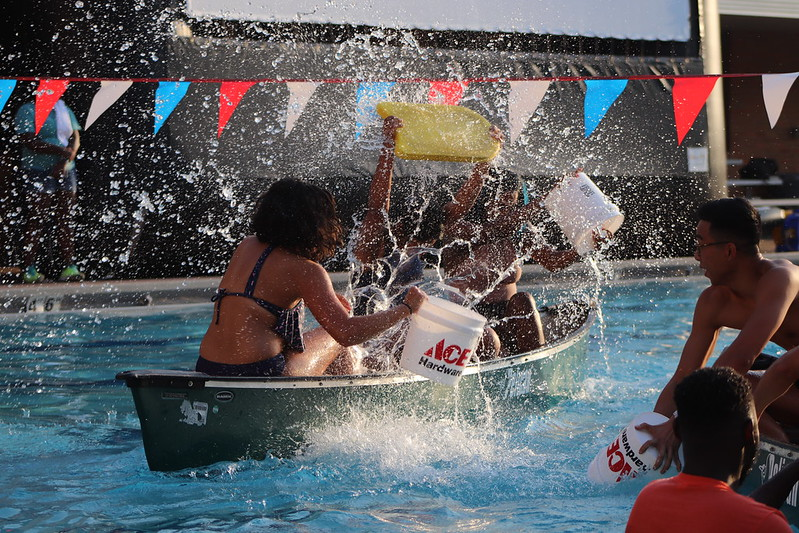 Students spashing each other on a kayak at the UTA outdoor pools