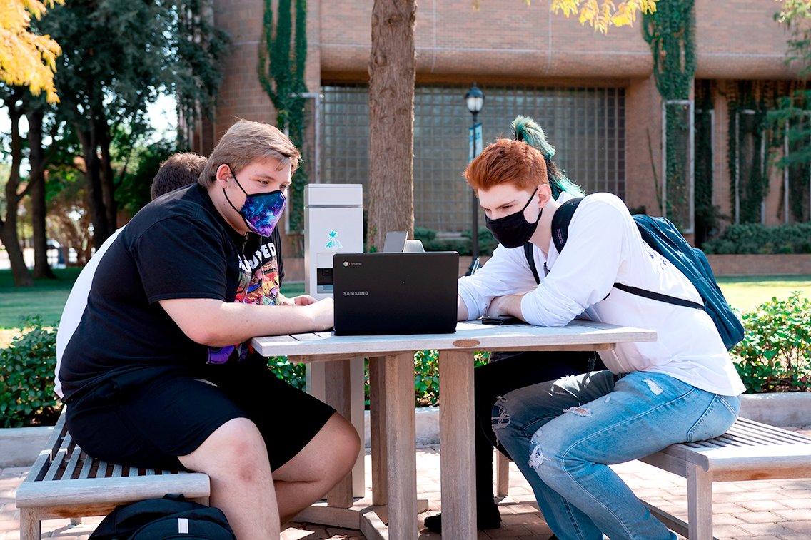 Students on a bench with face masks looking at a laptop