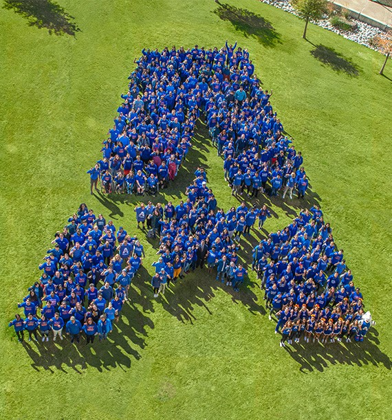 group of people gathered to form the UTA logo