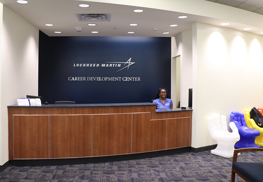 office front desk with student standing wearing blue