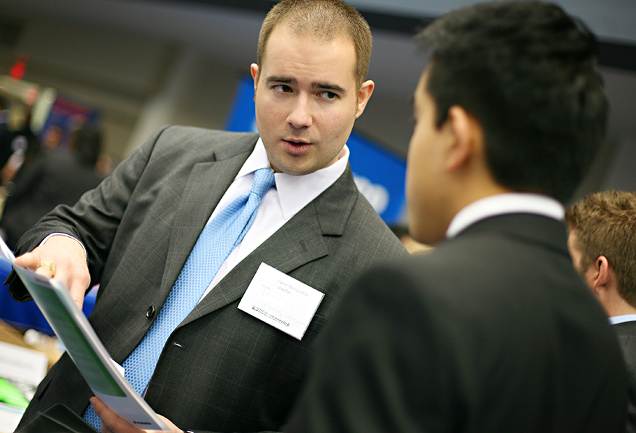 man with file talking to student in suits