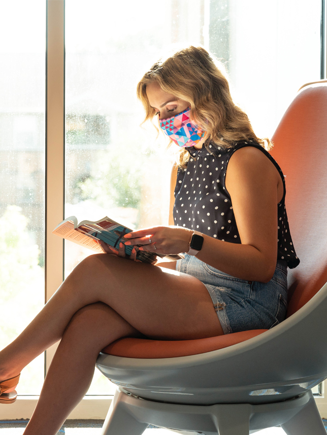 Girl wearing mask sitting in a chair reading a magazine.