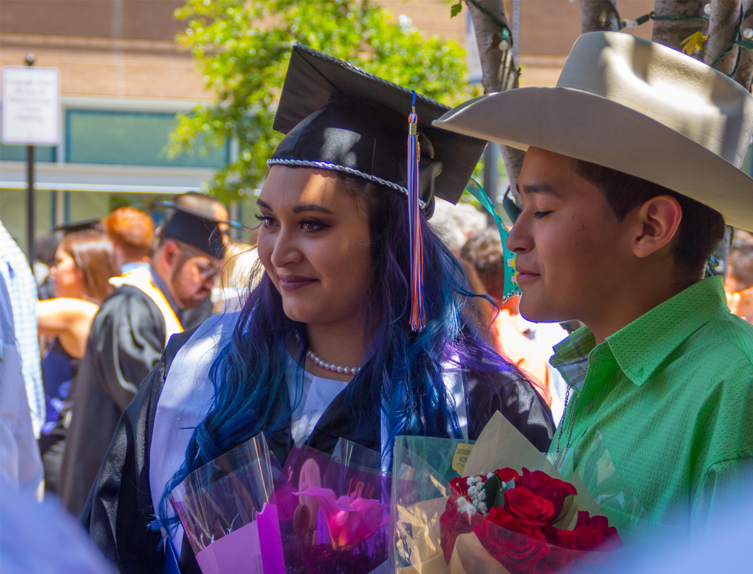 Woman with purple and blue hair in a graduation cap and gown posing with a boy in a cowboy hat.