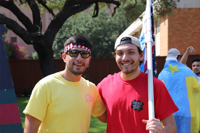 Two members of the Interfraternity Council holding various flags