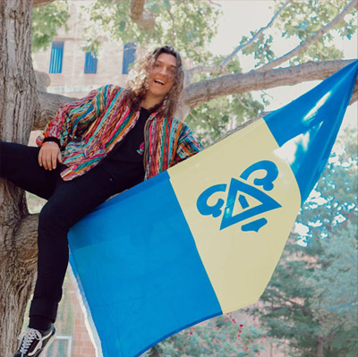 Fraternity member on a tree branch holding a flag
