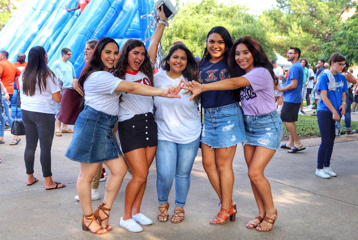 A small group of sorority sisters posing and making sorority like hand signs.