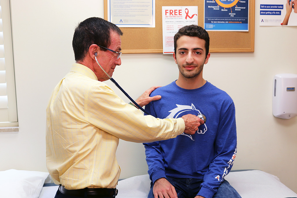 A patient being examined by a doctor using a stethoscope
