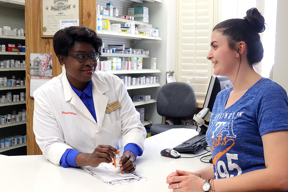 A person sitting at a desk with a pharmacist