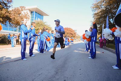 Man running in 5k as he passes by adoring fans on the side.