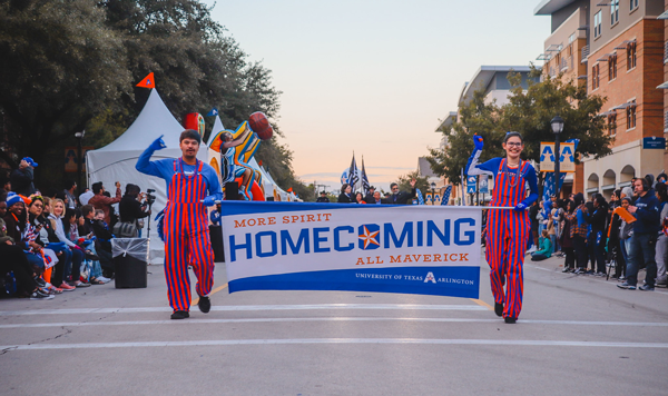 Two UTA students walk in the Homecoming parade while holding a Homecoming banner