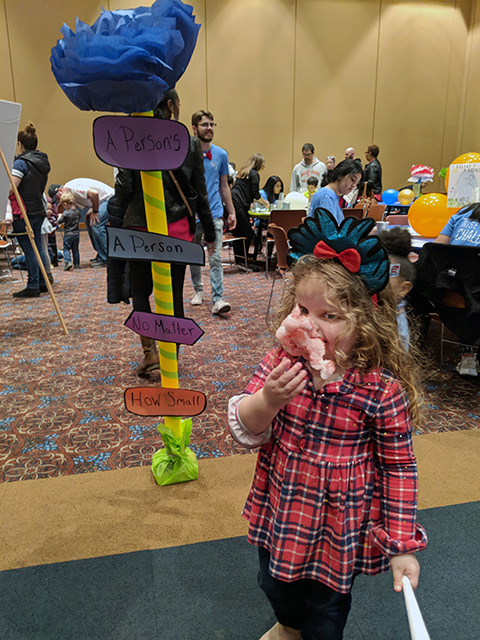 A girl eating candy at Dr Seuss Event