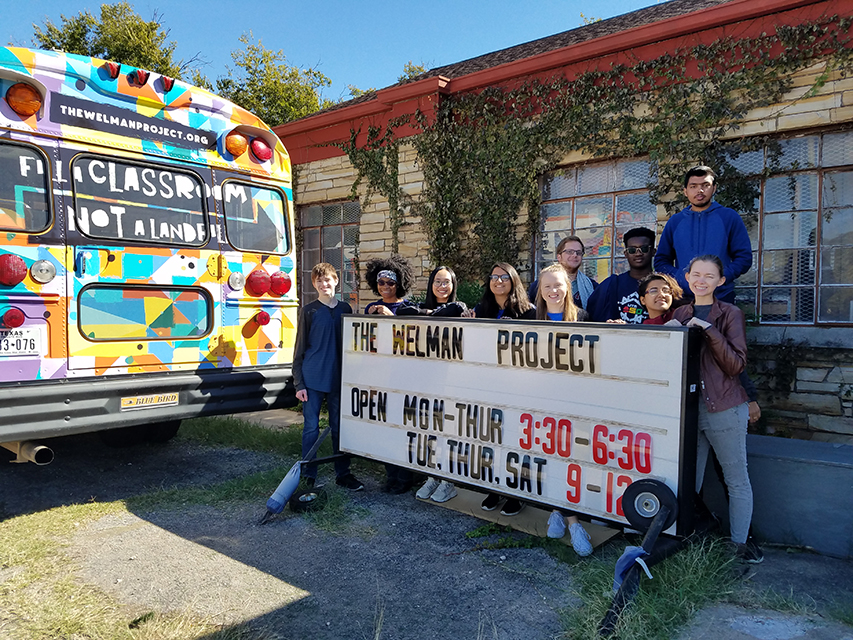 UTA Volunteers group at Wellman project posing with a colorful bus