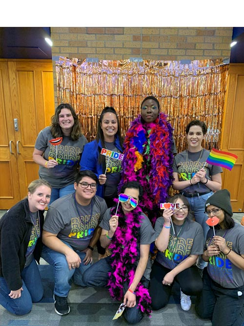 Pride Peers at a photo shoot with rainbow-colored props