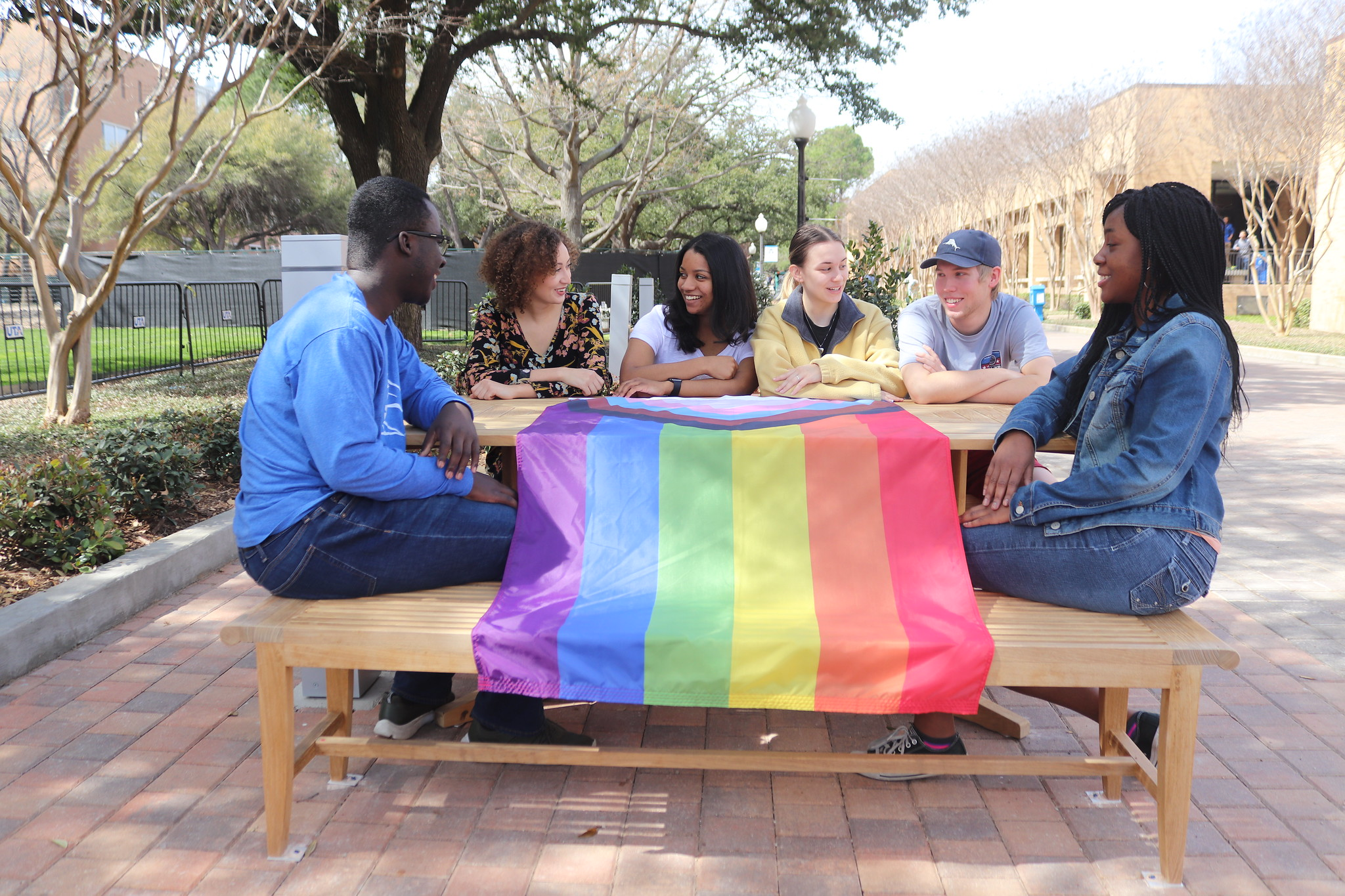 UTA students sit around a table that is covered with a pride flag at UTA