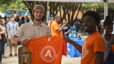 two students holding up U T A t-shirt