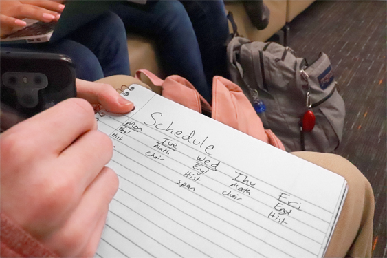 Student writing class schedule down on paper