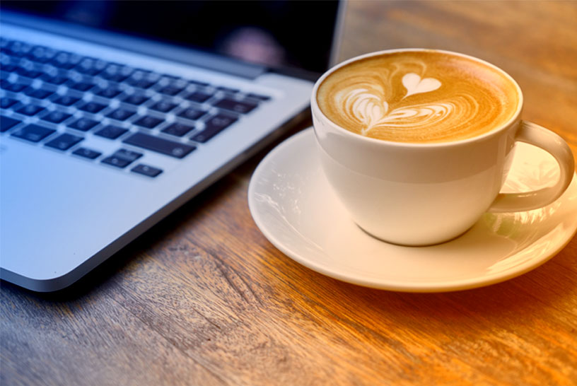 A cup of coffee next to a computer.