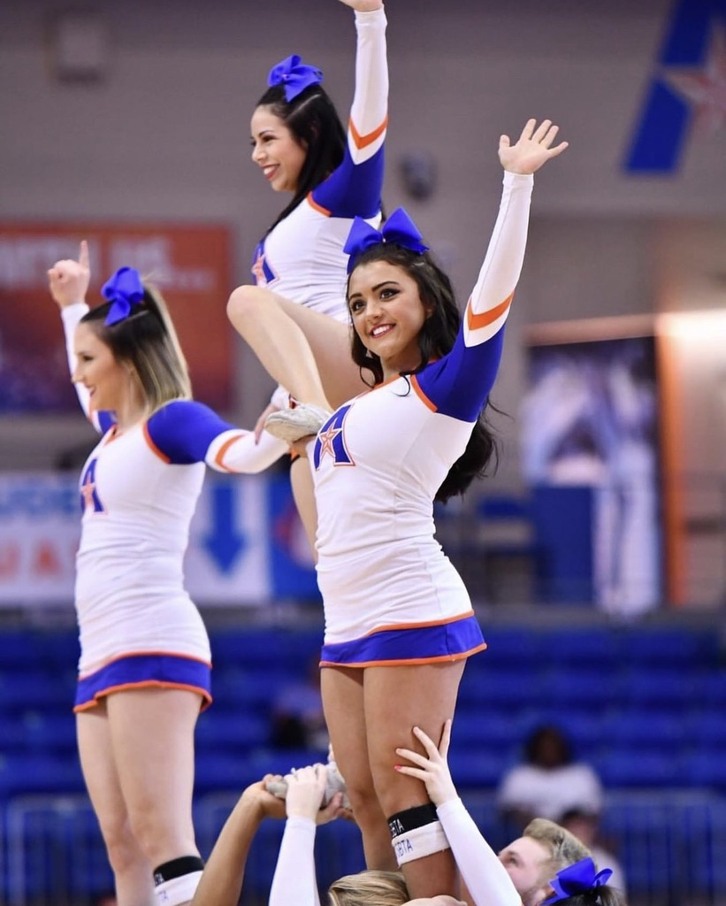 Cheerleaders performing with one in the air