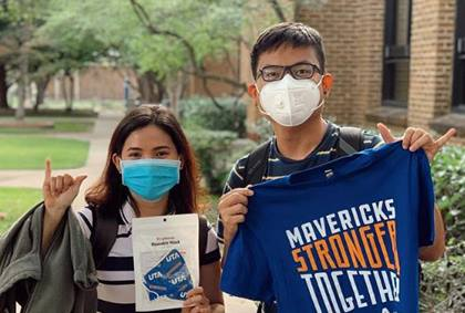 Students with masks on holding a t-shirt