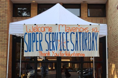 A tent holding up a sign labeled 'Welcome Mavericks to SUPER SERVICE SATURDAY Thank You for Volunteering'
