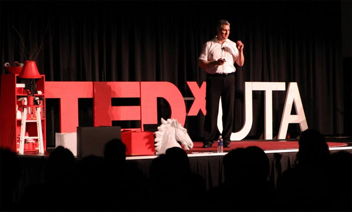 Man, in formal attire, speaking to audience at TEDxUTA