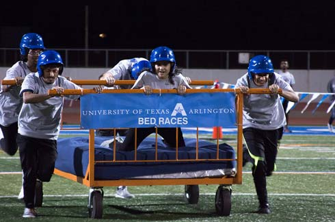 4 students run down Maverick Stadium rolling a bed on wheels with one student lying on it
